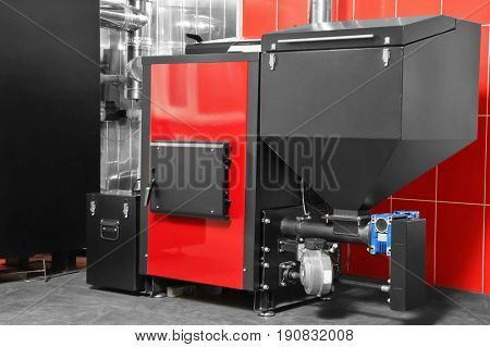 Solid fuel boiler against red wall