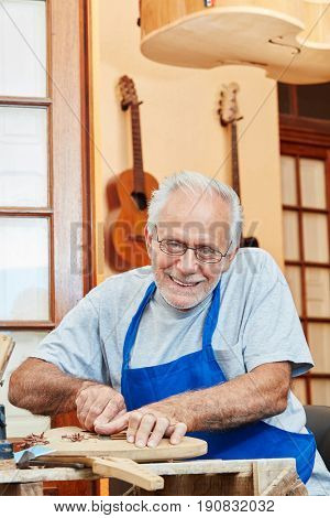 Senior citizen as luthier master working with experience on new guitar