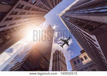 plane flying over multiple office skyskraper in the sun, Manhattan, New York City
