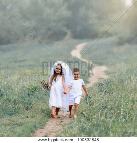 Young bride and groom playing wedding summer foggy morning outdoor. Children like newlyweds, kid's game. Bridal, wedding concept, image toned and noise added.