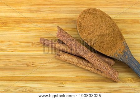 Cinnamon powder on wooden spoon next to Cinnamon sticks made of inner bark on wooden background with copyspace