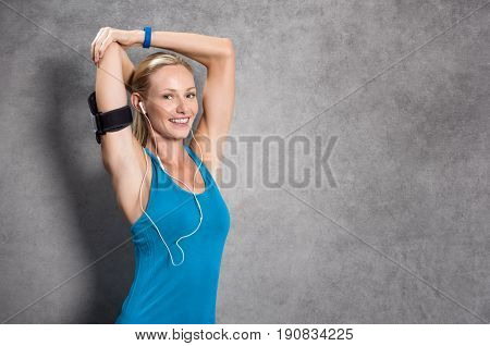 Happy young woman doing stretching while listening to music on earphones. Happy sporty woman smiling on grey wall and looking at camera. Cheerful girl in sportswear doing stretching with copy space.