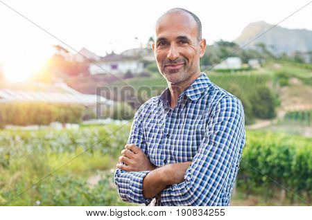 Portrait of a proud mature farmer standing with folded arms with vineyard in background. Mature satisfied winemaker looking at camera. Proud owner of the vineyard with crossed arms.
