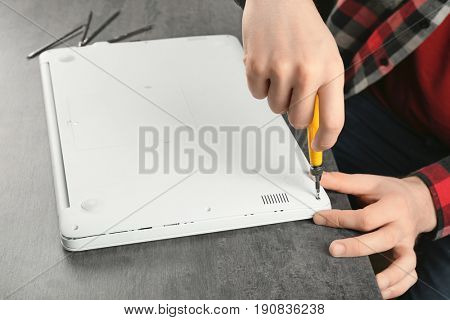 Male hands assembling laptop body on table. Concept of computer repair