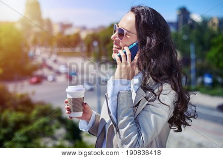 Mid shot of graceful woman talking on phone while drinking coffee on top of building