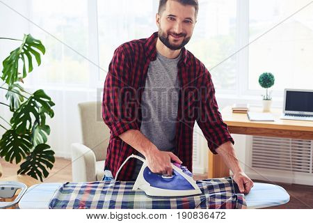Mid shot of muscular guy ironing attentively shirt on ironing board