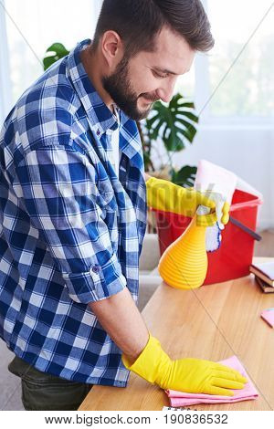 Vertical of caring guy pulverizing and dusting working place in bright room