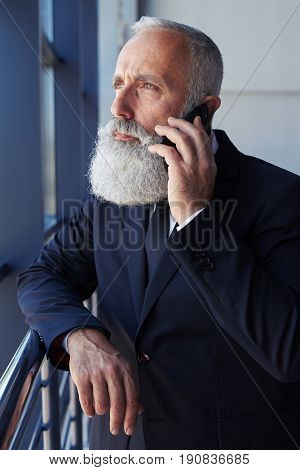 Vertical of severe sir talking on phone while looking out window while leaning on handrail
