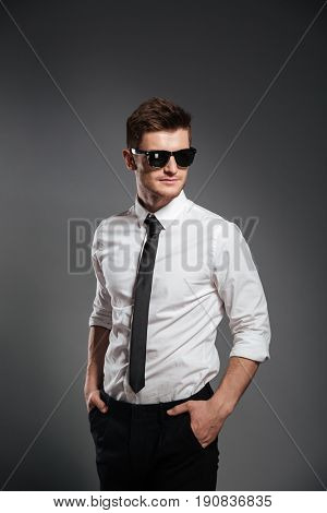 Photo of serious young man dressed in formalwear wearing sunglasses standing isolated over grey wall. Looking aside.