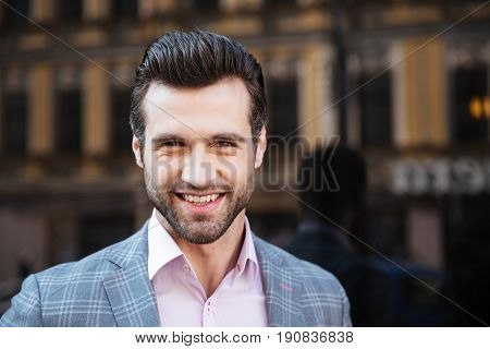 Close up portrait of a smiling handsome man in a jacket looking at camera in a city area