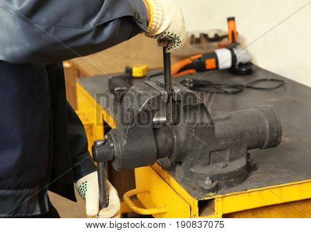Man using grip for metalworking in shop
