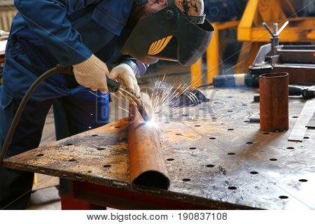 Worker using welding equipment for metalworking in shop