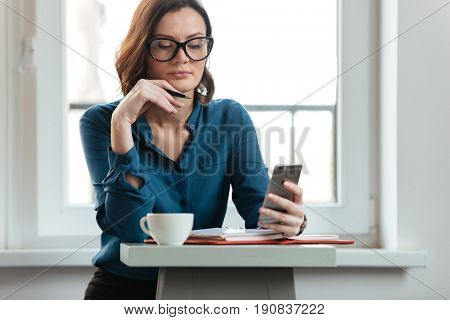 Portrait of a confident young woman in glasses at the cafe table holding mobile phone and making notes in notepad