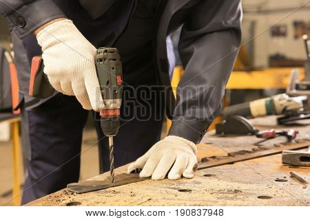 Worker using drill for metalworking at shop