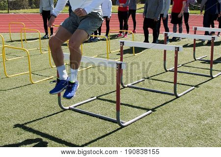 High school track and field athletes jumping over hurdles during a power strength practice