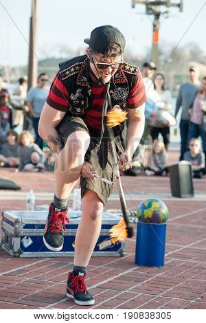 BALTIMORE INNER HARBOR, MD - FEBRUARY 18: A Street performer entertains crowd with juggling act on February 18, 2017