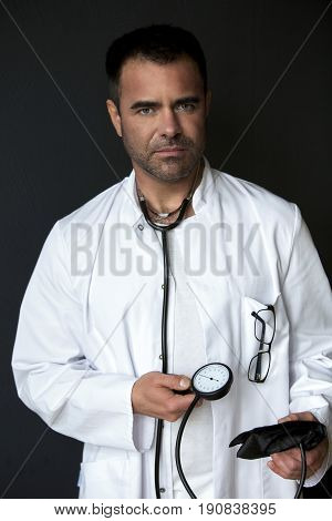 handsome doctor holding a sphygmomanometer and looking thoughtful
