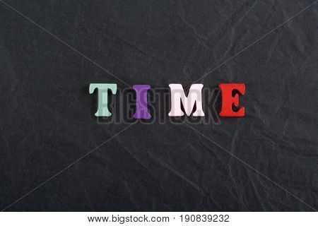 TIME word on black board background composed from colorful abc alphabet block wooden letters, copy space for ad text. Learning english concept
