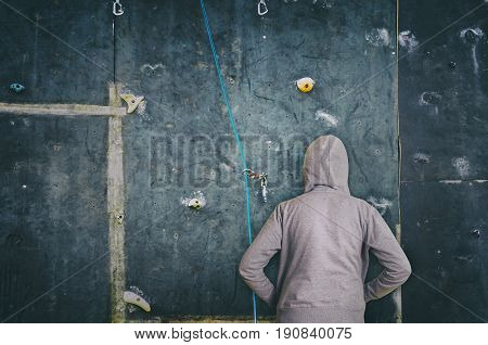 Rear view of hooded man against artificial rock climbing wall. Concept of overcoming obstacles and success.