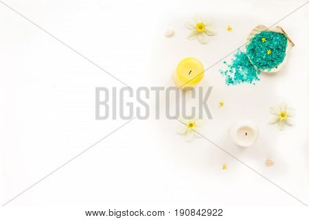 Beauty spa composition. White and yellow candles iris flowers sea shells and sea salt on white background. Flat lay top view copy space