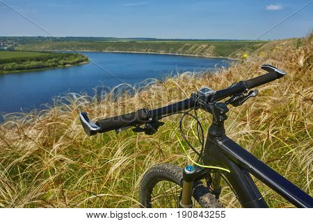 Close-up of helm of the mountain bicycle in the green grass against beautiful landscape. Detail of the bicycle and nature. Horizontal photo. Extreme travel in the countryside. Sporty backgrounds. Concept of the healthy lifestyle.