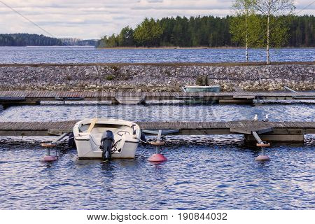 White motor boat and green oar boat pier in finnish nature lake landscape with birch trees