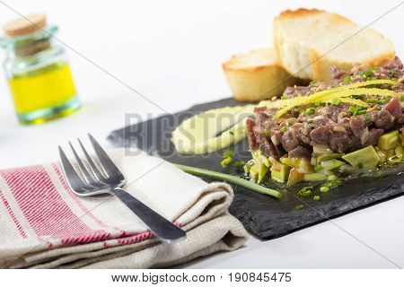 Bluefin Tuna Tartare On A Black Slate Plate With Avocado.