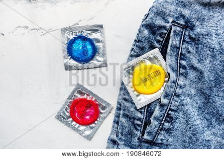 condoms and jeans for male contraception and birth control on white background top view