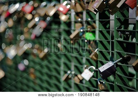 Close-up of a large number of padlocks attached to metal bridge railing across river l'Arve in Chamonix