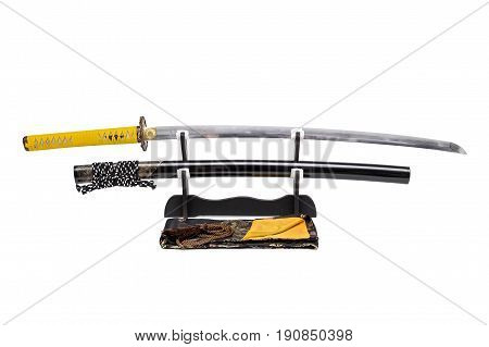 Japanese sword with yellow leather cord wrapped on handle and scabbard with ray skin on stand white background black silk bag at front.
