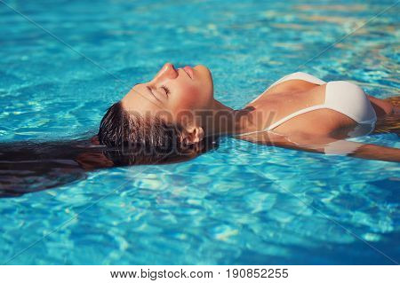 Portrait Of Beautiful Tanned Woman In White Swimwear Relaxing In Swimming Pool Spa. Hot Summer Day A