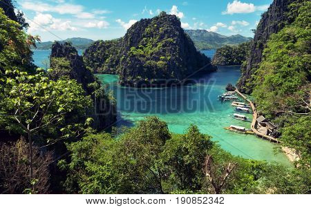 Elevated view of lagoon with boats surrounded by rocks and turquoise sea. Coron. Palawan