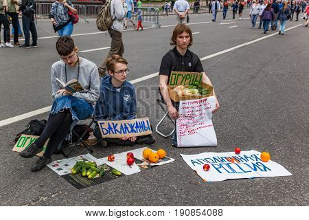 12 June 2017. Russia. Moscow. Saharova st. Protest by Alexei Navalny. Three young people holding posters about apolitical Russia. They are talking that people not interested in politics in country.
