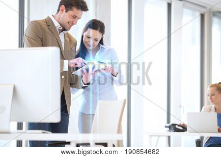 Business people using tablet computer with female colleague in background at office