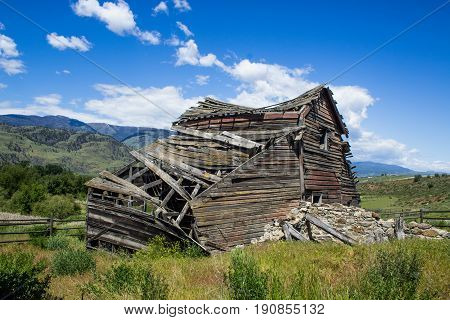 Weathered Old Barn Collapsing Under a Blue Sky in the Old West