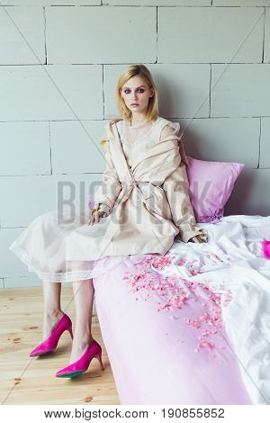 A beautiful blond woman in a taffeta dress and a beige trench coat pink shoes sits on a bed with pink bed linen. Fashion model. Fashion photo concept
