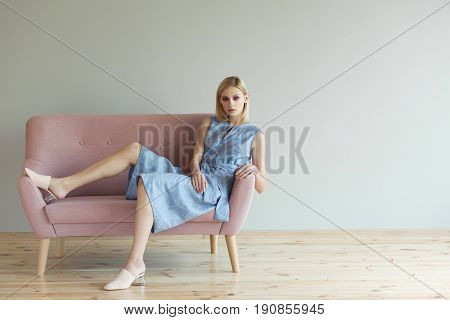 Beautiful blond woman in blue overalls in a light pink shoes sitting on a pink sofa. Fashion model. Fashion photo concept
