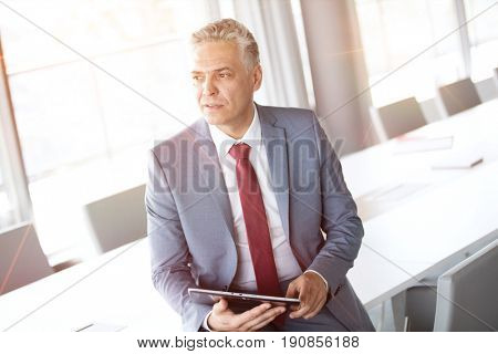 Thoughtful mature businessman holding digital tablet while leaning on conference table