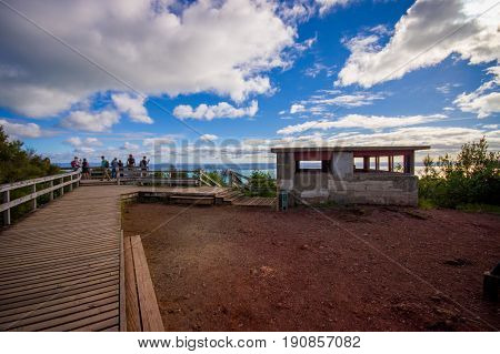 People enjoying the beautiful view from top in the mountain in Rangitoto Island wlaking in wooden paths, New Zealand in a sunny day.