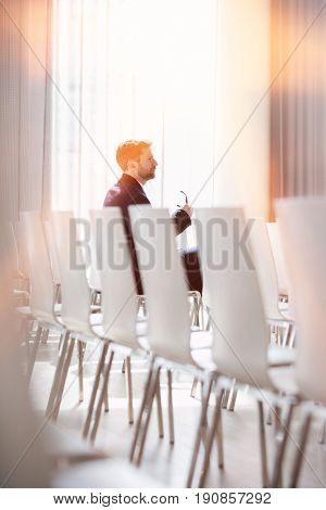 Side view of businessman holding eyeglasses while sitting in seminar hall