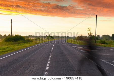 The Ghost Runs Across An Empty Country Road In Search Of Shelter From The Sunrise In Summer