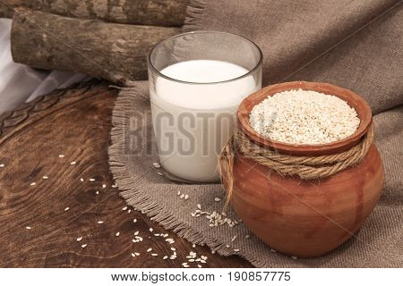 Vegan sesame milk in glass and white sesame seeds in a clay pot on a wooden table. Raw food diet. Horizontal photo. Selective focus.