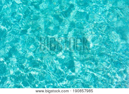 background textures of close up of blue and white water ripples and reflections of light in the swimming pool