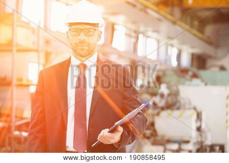 Portrait of confident mid adult male supervisor holding clipboard in metal industry