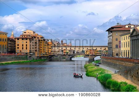 Florence, Italy - June, 5, 2017: embankment of Arno river in Florence, Italy with Ponte Vecchio bridge over the river