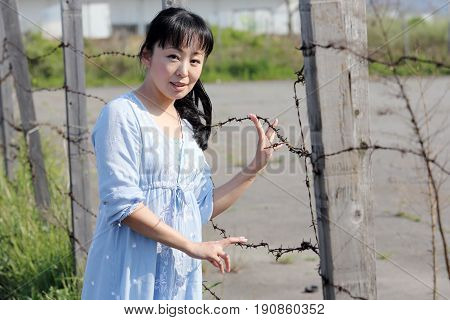 beautiful young asian woman stands at a barbwire fence
