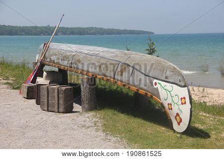 A voyageur canoe turned upside down a beach of Straits of Mackinac
