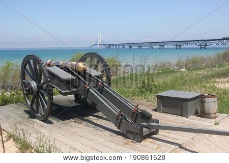 A cannon on the shores of the Straits of Mackinac with the Mackinac Bridge in the background