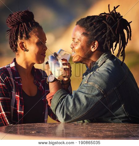 Interracial couple making a toast with interwined arms while looking into each others eyes with cheerful smiles as they enjoy their first outdoor date while seated at a public picnic table in Africa.
