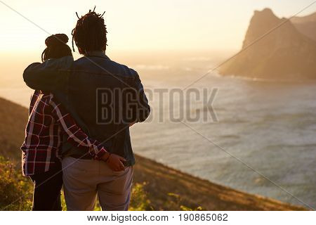 Casually dressed mixed race couple embracing each other while enjoying the awesome view of the ocean and mountains in front of them, taken from behind with the womans hand in the mans back pocket.